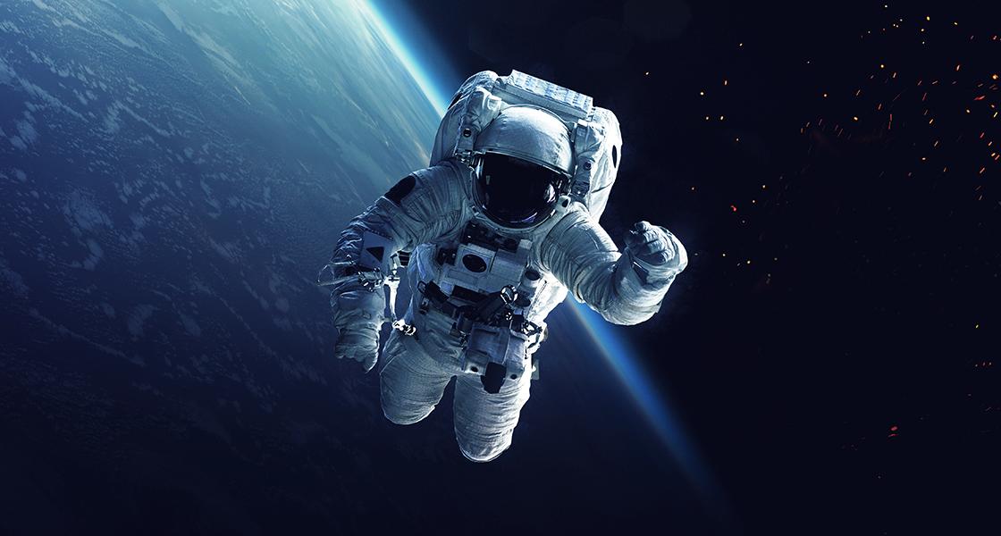 Astonaut and space shuttle orbiting Earth